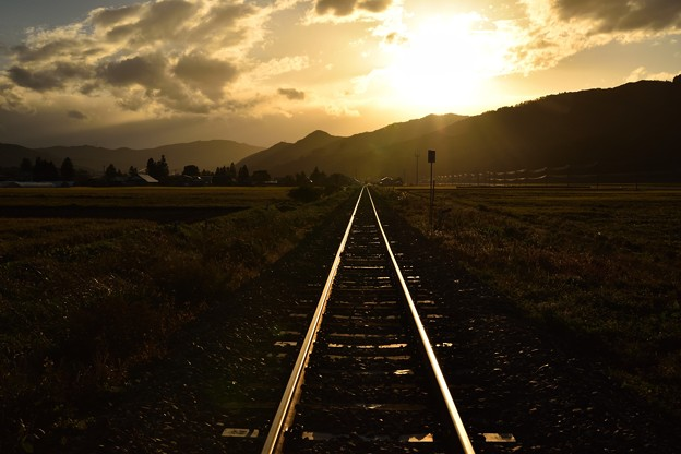 秋の夕暮れに輝く鉄路