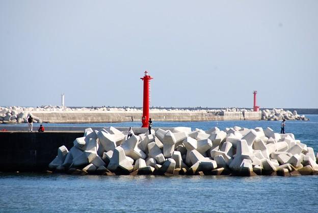 真っ赤な灯台と真っ白な波消しブロック