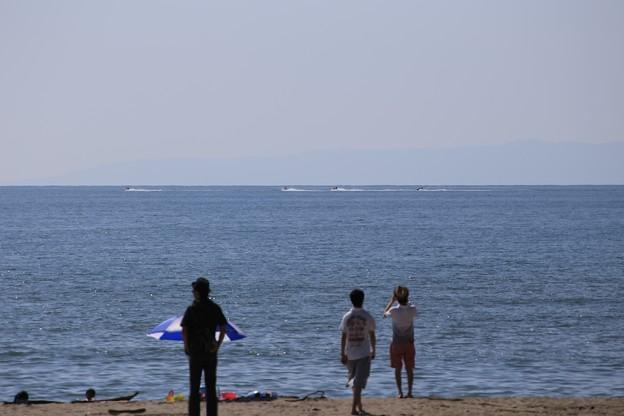 沖を走る水上バイクを見つめる人たち