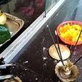 Photos: お供え物 緑の上がカレーです、リスの灯明は油に芯を浸したものです