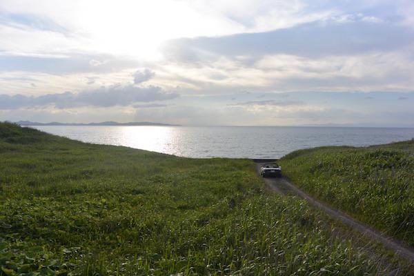 横にそれて夕日迫る陸奥湾へ続く道へ