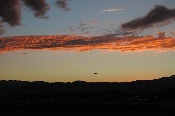 途中 夕焼けの中で着陸態勢の飛行機を眺め