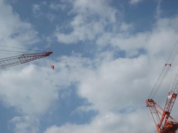 雲の広がる空に働く重機
